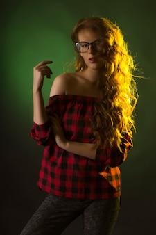 暗闇の中でスタジオで眼鏡をかけたファッショナブルな若い女性