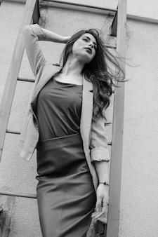 大都会の風の強い屋根の階段で、薄手のジャケットと革のスカートを着てポーズをとるファッショナブルな若い女性。黒と白。
