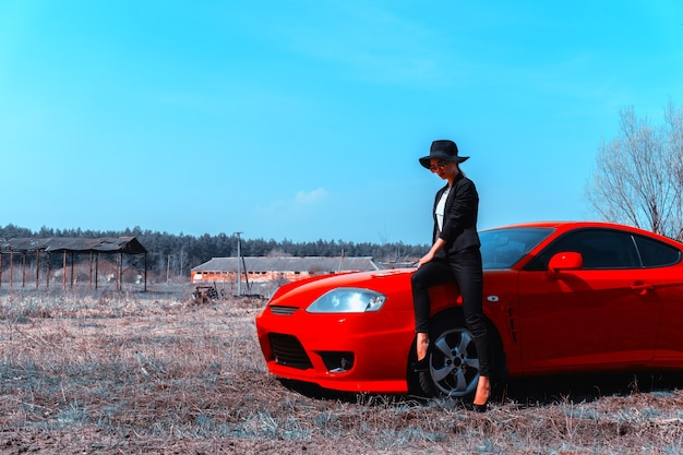 Fashionable young lady in sunglasses and hat with wide brim sits on a red sport car in the field