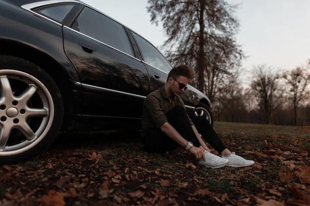 옷과 흰색 운동화의 유행 젊은이가 현대 검은 차 근처에서 쉬고 있습니다.