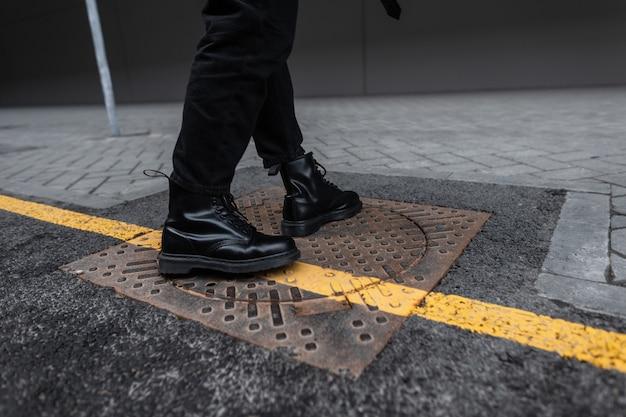 トレンディなジーンズのヴィンテージレザーブラックブーツのファッショナブルな若い男は、街の鉄のハッチに立っています。スタイリッシュな季節の靴の男性の足のクローズアップ。イエローラインのストリートスタイル。若者のファッション。