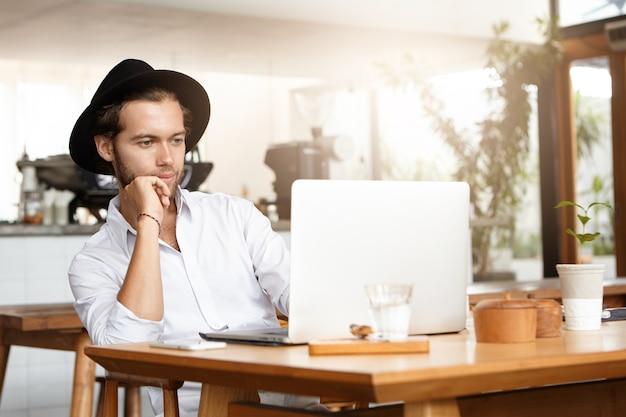 ファッショナブルな若い男が彼の一般的なラップトップで電子書籍を読んで、彼の肘に寄りかかって興味を持って見ています。コーヒーブレーク中に休憩を楽しんで、リモート作業にノートブックpcを使用する自信のあるフリーランサー