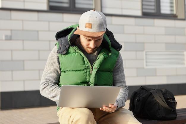Viaggiatore alla moda giovane seduto sulla panchina con borsa, che tiene il computer portatile sulle ginocchia, prenotazione appartamento durante il soggiorno in città straniera in viaggio d'affari. tecnologia, viaggi e stile di vita