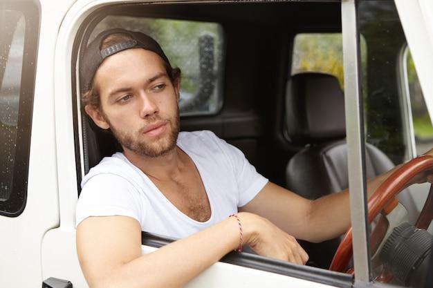 スナップバックを身に着けているファッショナブルな若い男が彼のスポーツユーティリティ車を運転し、彼の頭と肘を開いた窓から突き出して、心配そうな表情で道路を見て