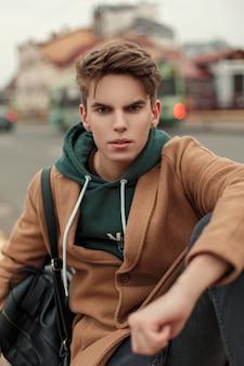 까마귀와 거리에 검은 가방이있는 빈티지 코트에 머리를 가진 유행 젊은이