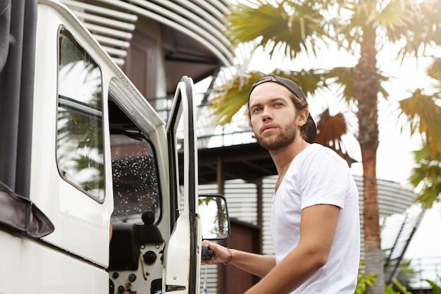 白いtシャツと野球帽を身に着けているスタイリッシュなひげを持つファッショナブルな若い男が、彼の4輪駆動車に乗りながら自信と誇り高い顔の表情で目をそらしています。