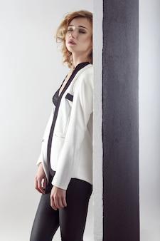 Модная молодая модель позирует возле черной стены, раздевая белую куртку и закрытые глаза. внутренний снимок, серая стена