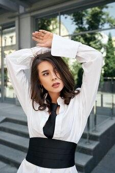Модная молодая модель позирует возле здания.