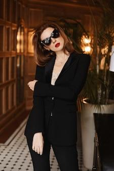 エレガントな黒のスーツと黒のサングラスでファッショナブルな若いモデルの女性。美容、ファッション。光学およびアイウェア