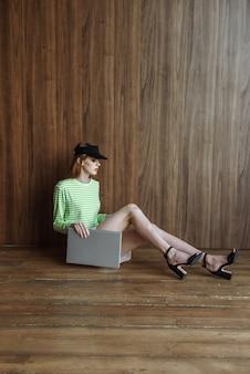 床に座っているスタジオでラップトップでポーズをとってファッショナブルな若いモデルの女性