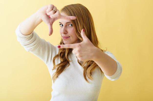 赤い手入れの行き届いた爪を身振りで示す、彼女の指でカメラフレームを作る、あなたのテキストや広告のための空白の黄色のコピースペースの壁の背景に対して隔離されたポーズでファッショナブルな若いポジティブな女性