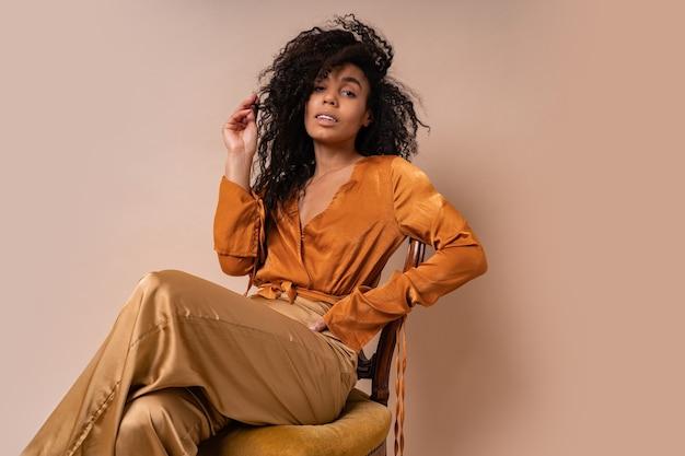우아한 오렌지 블라우스와 빈티지 의자 베이지 벽에 앉아 실크 바지에 완벽한 곱슬 머리를 가진 유행 젊은 매혹적인 아프리카 모델.