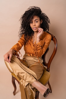 エレガントなオレンジ色のブラウスとヴィンテージの椅子ベージュの壁に座っているシルクのズボンの完璧な巻き毛を持つファッショナブルな若い魅惑的なアフリカのモデル。