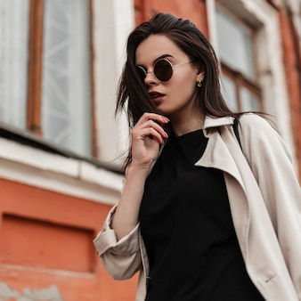 Fashionable young sexy woman in round stylish sunglasses in trendy casual wear on street in city. fresh fashion portrait pretty attractive girl in spring outfit outdoors. beauty gorgeous lady.