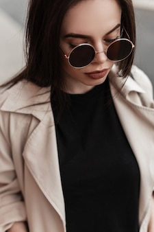 Fashionable young sexy woman in round stylish sunglasses in trendy casual wear on street in city. fresh portrait pretty attractive girl in spring outfit outdoors. beauty lady.