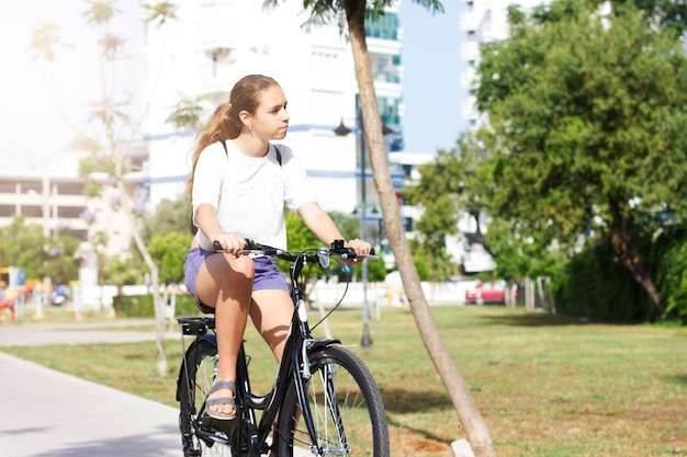 Fashionable young teen girl in shorts and t-shirt rides a bicycle in a summer park
