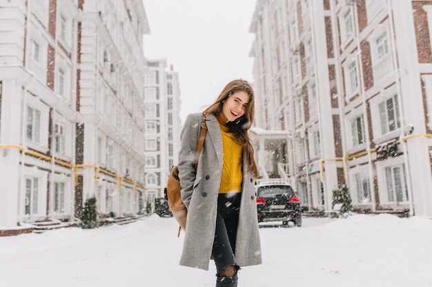 Fashionable young woman in coat with backpack walking on street in big city in snowing time. cheerful mood, snowfall, waiting for christmas, expressing positivity, true emotions.