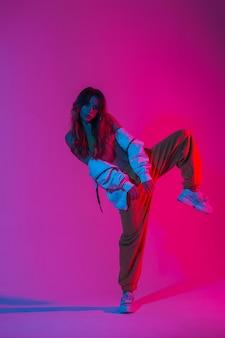 패션 운동화에 트렌디한 스포츠 청소년 옷을 입은 세련된 젊은 여성 댄서는 밝은 분홍색 빛으로 스튜디오의 한쪽 다리에 서 있습니다. 컬러 네온 컬러로 방에서 춤을 추는 세련된 소녀.
