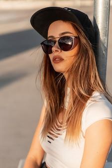 スタイリッシュなサングラスの流行の野球の黒い帽子のファッションカジュアルなtシャツのファッショナブルな若い女性のヒップスターは、日没時にアスファルトに座っています。ユースウェアのかなり都会的なクールな女の子は、太陽の下で通りでリラックスします。