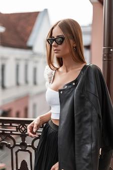 여름 날에 도시의 거리에서 포즈를 취하는 흰색 상단에 트렌디 한 블랙 가죽 재킷에 세련 된 선글라스에 세련 된 젊은 여자 소식통. 야외에서 휴식하는 매력적인 여자 모델. 청소년 스타일