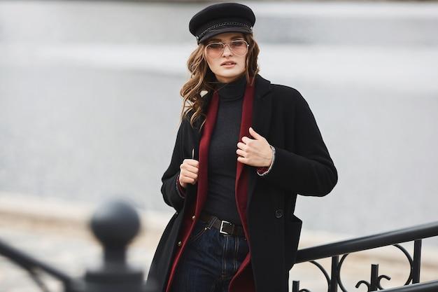 코트, 유행 모자, 선글라스는 도시 배경 위에 포즈 유행 젊은 여자. 유행 복장에서 아름 다운 모델 소녀 스트리트 패션의 개념입니다. 공간을 복사하십시오. 텍스트를위한 장소.