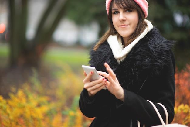 검은 코트를 입은 세련된 젊은 여성과 휴대 전화로 도시 거리를 걷는 니트 핑크 모자