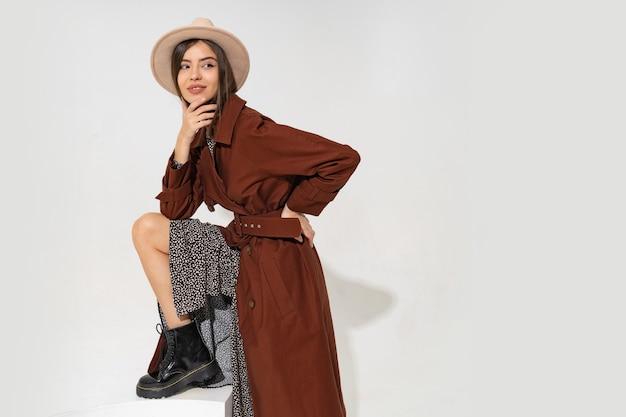 Модная молодая женщина в шляпе и модном зимнем пальто позирует
