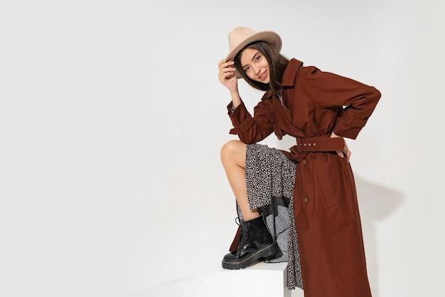 帽子とトレンディな冬のコートのポーズでファッショナブルな若い女性