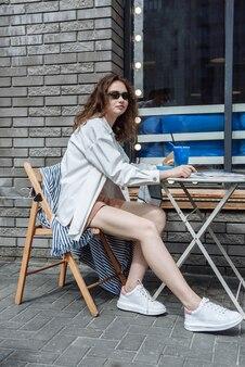 테이블에 있는 레스토랑에서 세련된 젊은 여성 모델