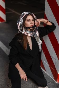 スタイリッシュでエレガントな服を着たファッショナブルな若い女性モデルは、サングラスを脱いでカメラを見ます。頭にシルクのスカーフを身に着けている季節のかわいい女の子は、通りのヴィンテージの縞模様の柱の近くに座っています