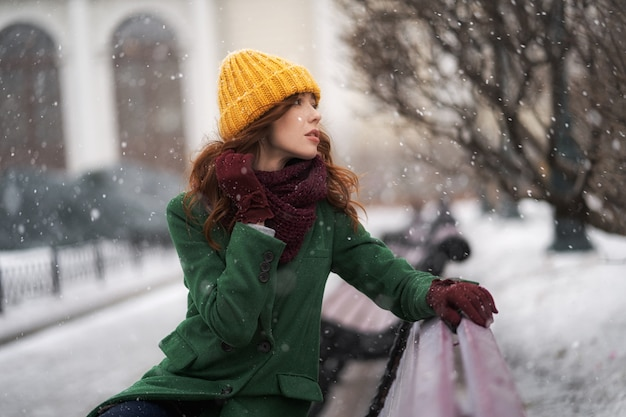 Fashionable young woman posing outside in a city street. winter portrait outdoors, in snowfall