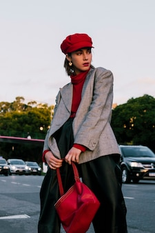 Fashionable young woman in red cap posing on road holding handbag