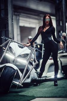 Модная молодая женщина, стоящая возле крутого индивидуального трайка