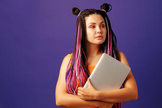 Модная молодая студентка с длинными афро-косами держит ноутбук на фиолетовом