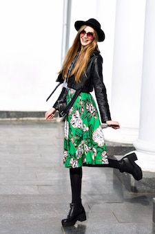 Giovane donna alla moda che cammina per strada con giacca di pelle e gonna floreale