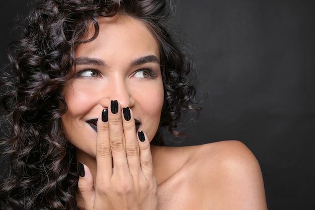 Модная молодая женщина с черным маникюром на темноте