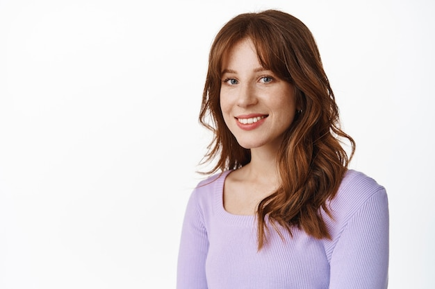 Fashionable young woman with freckles and white smile, standing in purple blouse with relaxed happy face expression