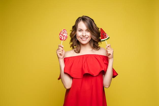 Модная молодая женщина с леденцом в руках на фоне