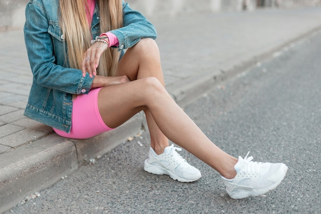 세련된 흰색 운동화에 분홍색 유행 반바지에 빈티지 데님 재킷에 긴 머리를 가진 유행 젊은 여자가 도시의 보도에 앉아있다. 여름 옷에서 여성의 신체의 클로즈업입니다.