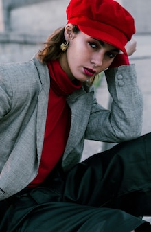 Fashionable young woman with red cap looking at camera