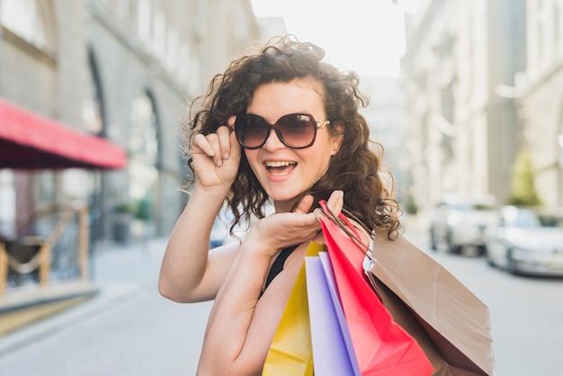 Giovane donna alla moda con gli occhiali da sole che trasportano i sacchi di carta