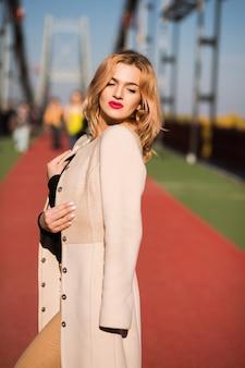 太陽に照らされて通りでポーズをとるおしゃれな服を着た素敵なモデル