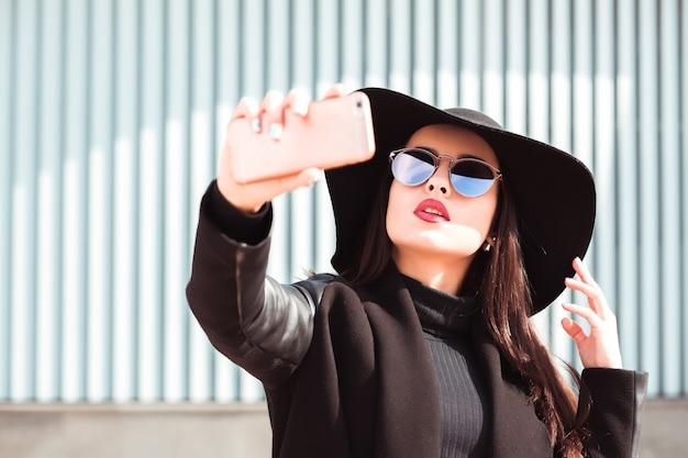 おしゃれな服を着た女性が帽子とサングラスを身に着け、携帯電話で自分撮りをしている