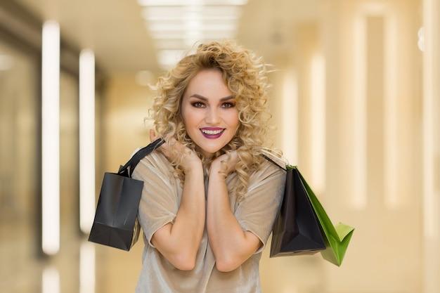 モールで買い物袋を持つファッショナブルな服を着た女性。ショッピングコンセプト