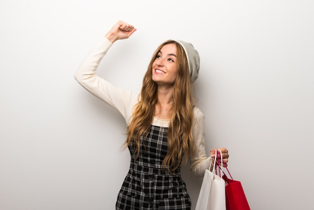Fashionably woman wearing hat holding a lot of shopping bags in victory position