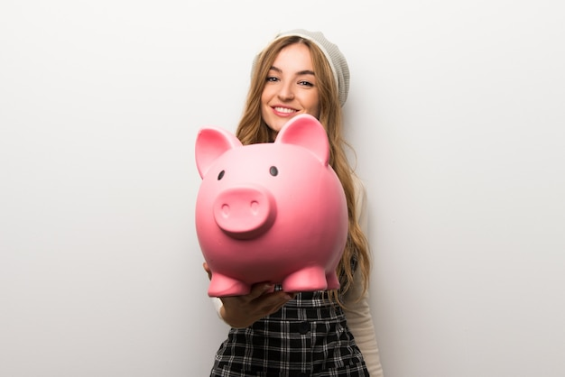 Fashionably woman wearing hat holding a piggybank