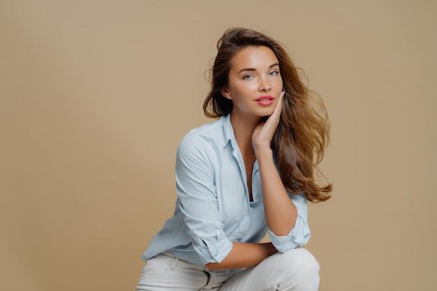 魅力的な若い女性は茶色の背景に座って、頬に触れ、fashionbaleの衣装に身を包んだ