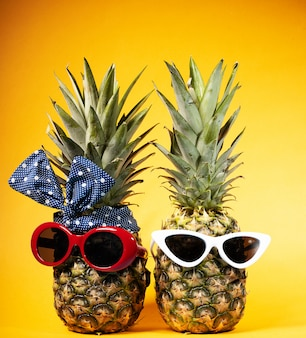 Fashionista in sunglasses on a yellow background. two pineapples with glasses