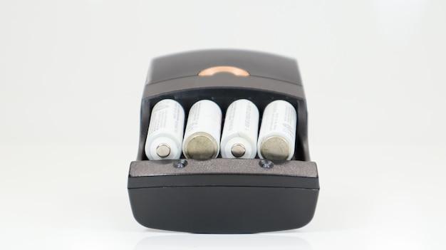 Быстрая зарядка батареек типа аа. перезаряжаемые батареи в черном зарядном устройстве с четырьмя ячейками на белом фоне.