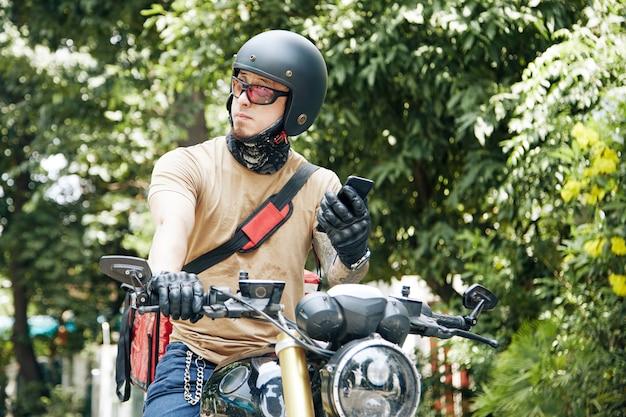 Сотрудник службы быстрой доставки катается на мотоцикле и осматривается в поисках дома ...